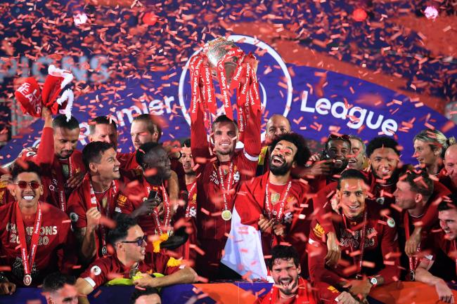 Liverpool captain Jordan Henderson (centre) lifts the Premier League trophy