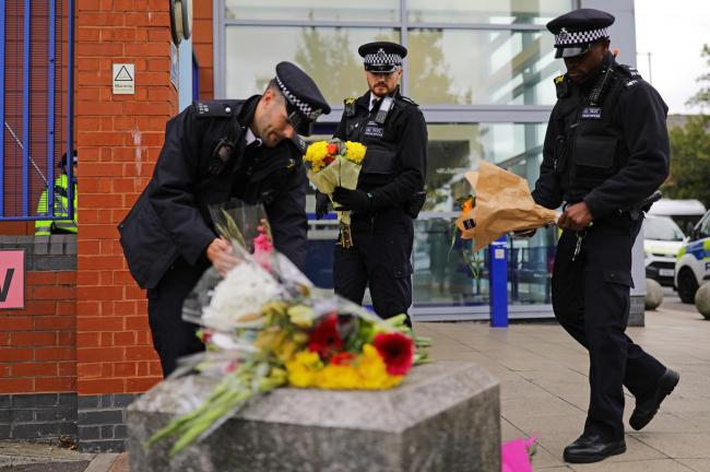 Met Police officers lay flowers outside Croydon Custody Centre. Credit: PA