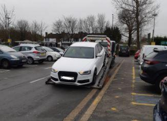An image of a white Audi being loaded onto a recovery truck. Credit: BCH Road Policing Unit