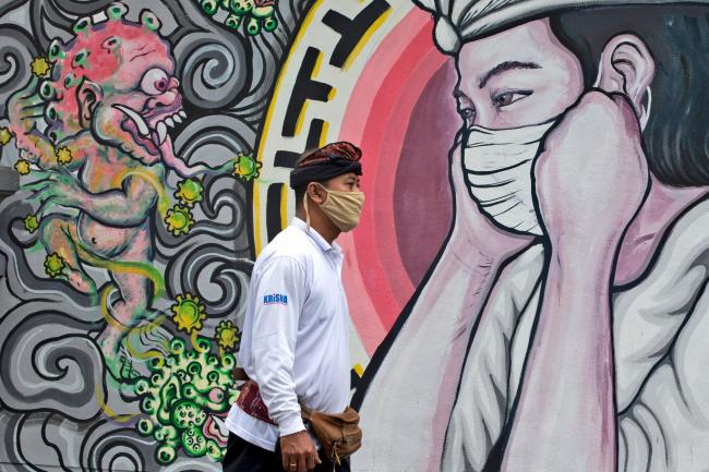 A man walks past a coronavirus-themed mural in Bali, Indonesia