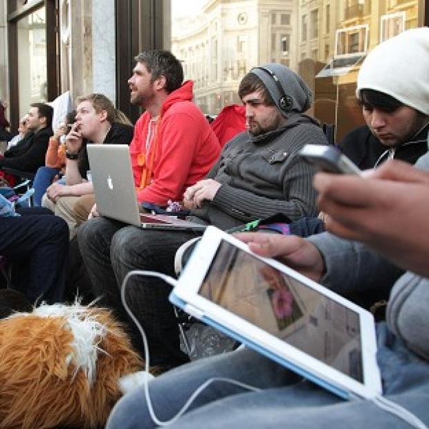 People sit in the queue for the new iPad 3 outside the Apple Store on Regent Street in London