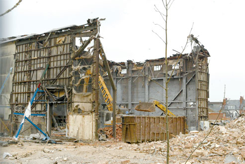 End of an era: Bulldozers tear into the building this week, leaving just the towering frontage
