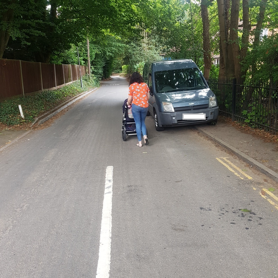 A woman is forced into the road with a buggy because the pavement is blocked