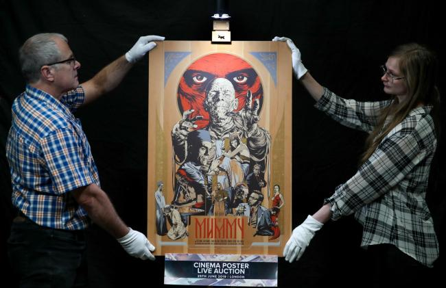 Prop Store employees adjust a Mondo poster printed on wood of the 1932 film 'The Mummy' Photo credit: PA